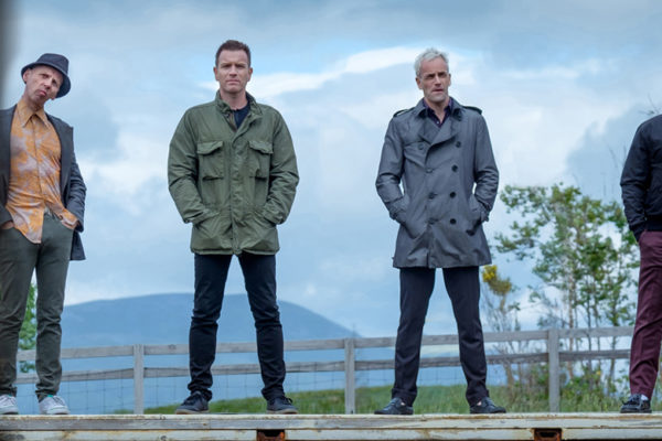 The Trainspotting foursome stand behind a train track